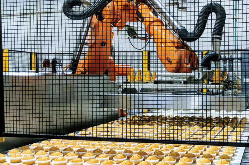 A robotic system depans two pans of muffins before they head to the cooler.