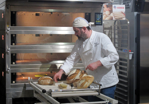 A baker pulls out loaves of rustic artisan bread from a deck oven at the Lab du Boulanger (Baker's Lab). (1 of 11)
