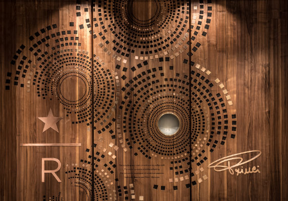 "The entry doors to the new Starbucks Reserve store are made of walnut and feature a brass-rimmed porthole and concentric circles borrowed from the art for a Starbucks Reserve coffee card. The doors are emblazoned with the Starbucks Reserve logo (a star and the letter R), the Princi bakery logo and these words: ""The complete and total commitment to coffee craft. The ancient practice of artisanal baking. The immersive experience of combined passions. Starbucks Reserve and Princi. Welcome."" (1 of 7)"