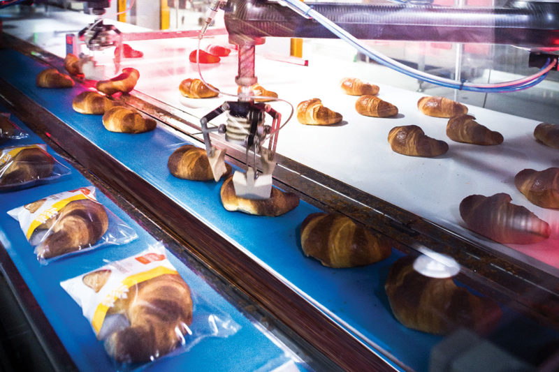 Robotics delicately pick and place croissants on a single-lane conveyor that feeds a horizontal wrapper.