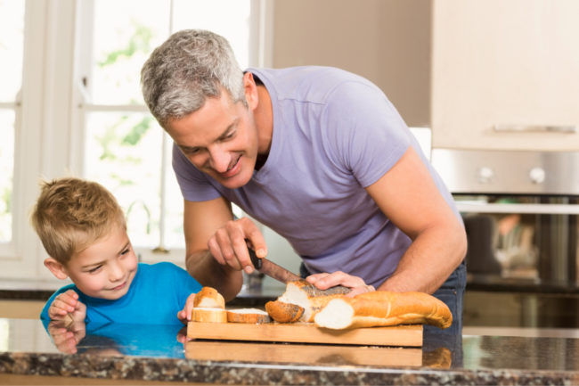 Father showing son how to slice bread
