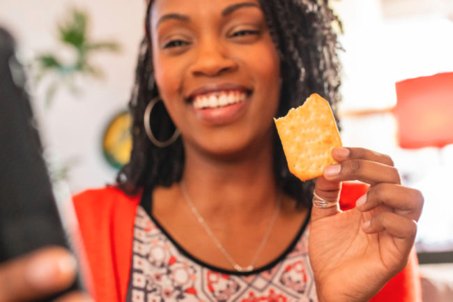 Woman snacking on Ritz crackers
