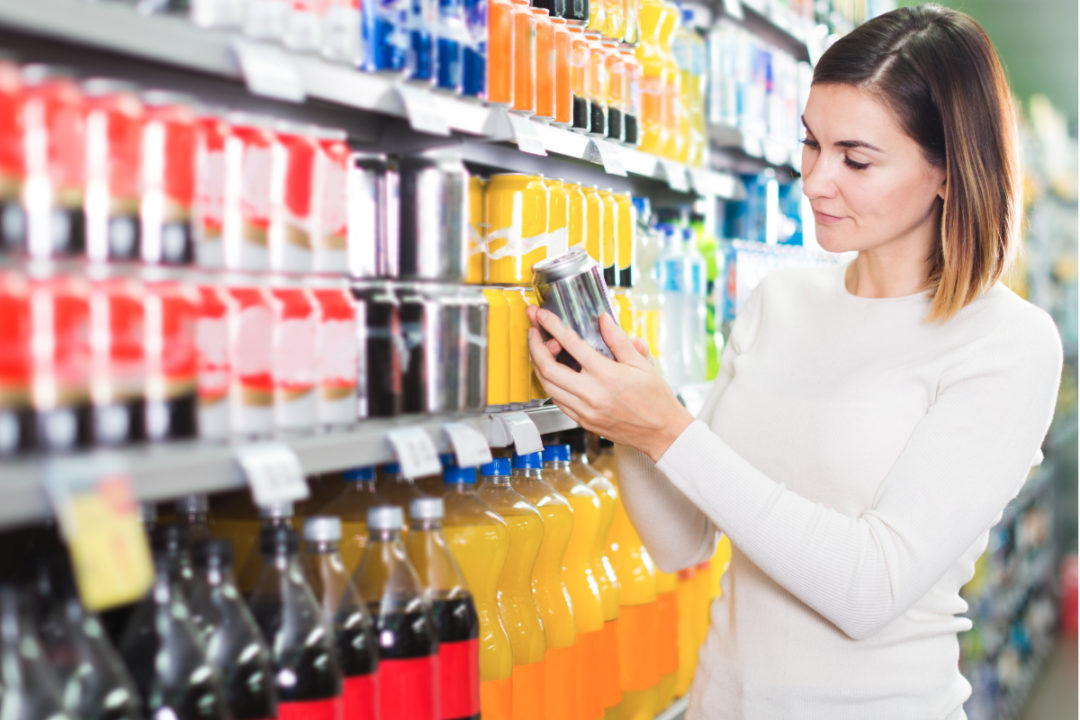 Woman buying soda in grocery store