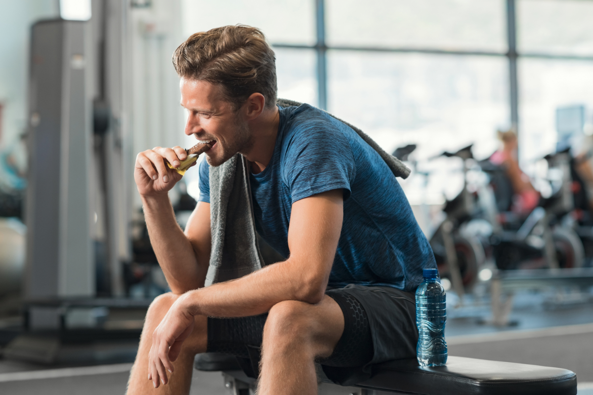 Athletic man eating protein bar at the gym