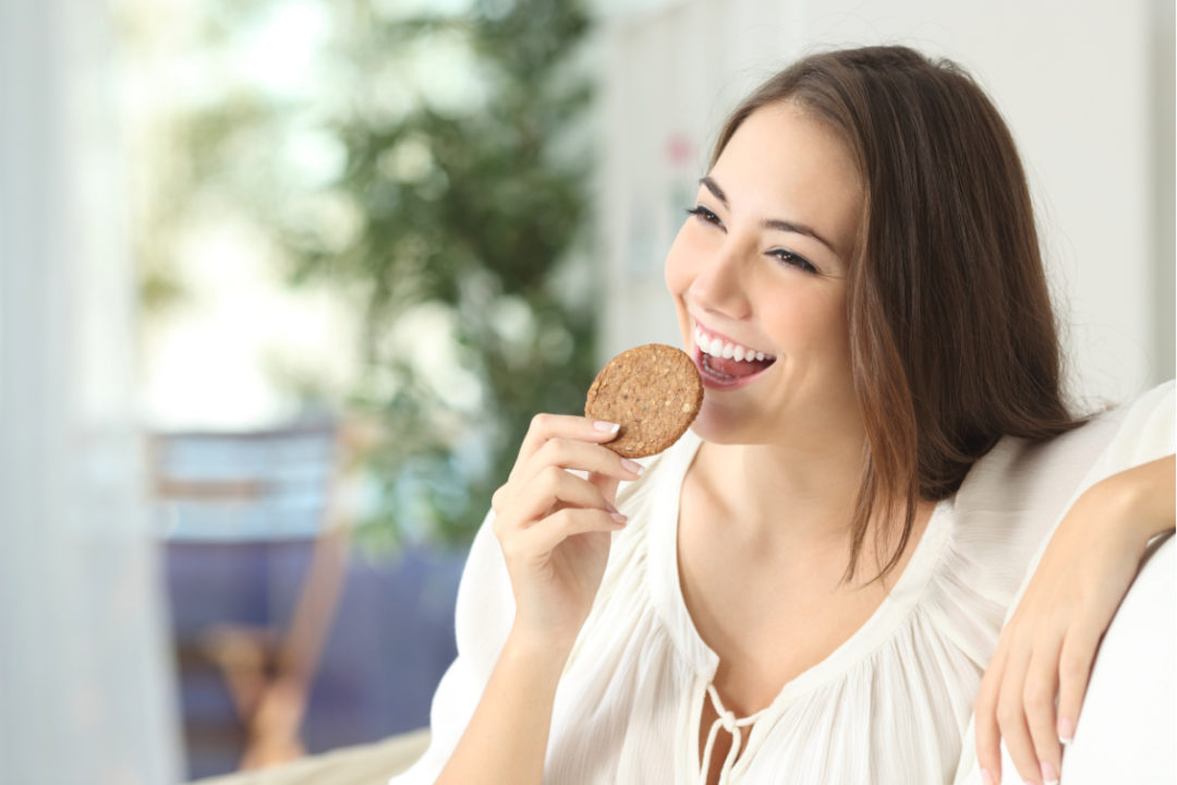 Woman eating a cookie as a snack