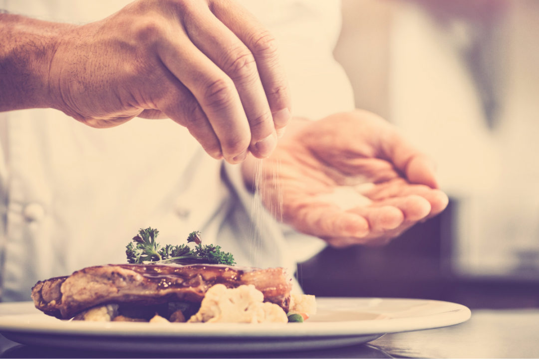Chef putting potassium chloride on a meal