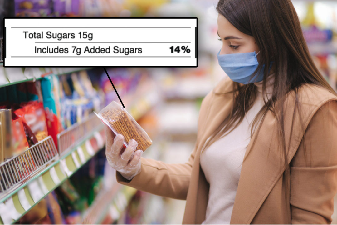 Woman reading added sugars label on crackers in supermarket