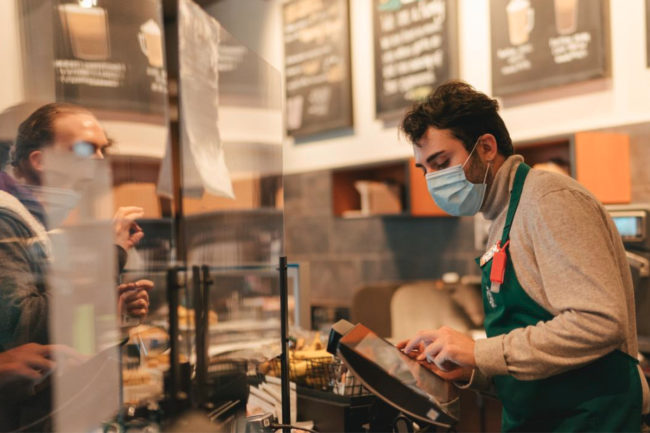 Starbucks employee in mask taking coffee order