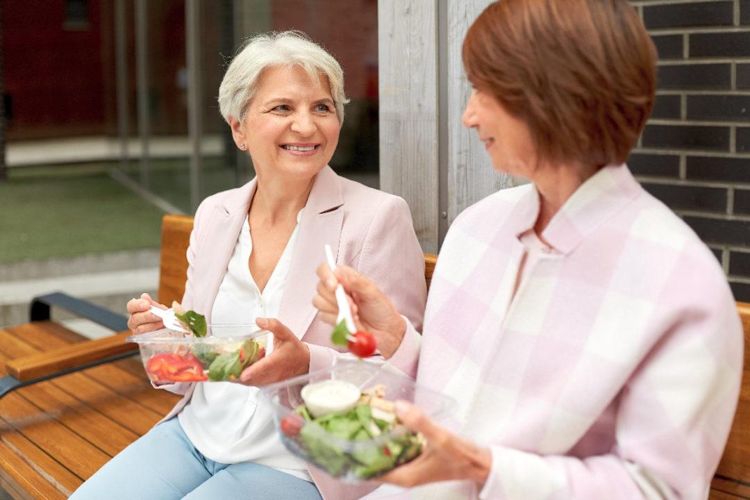 Two older women eating salad