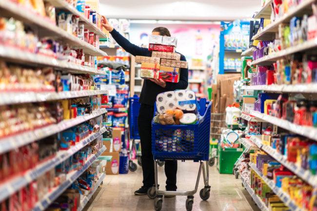 Man buying a lot of packaged foods at the supermarket