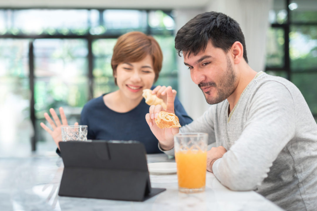 Couple eating at home while video calling friends