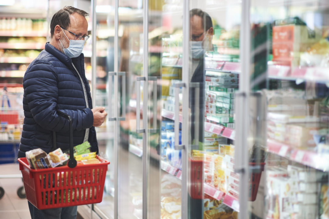 Man wearing mask shopping for frozen pizza