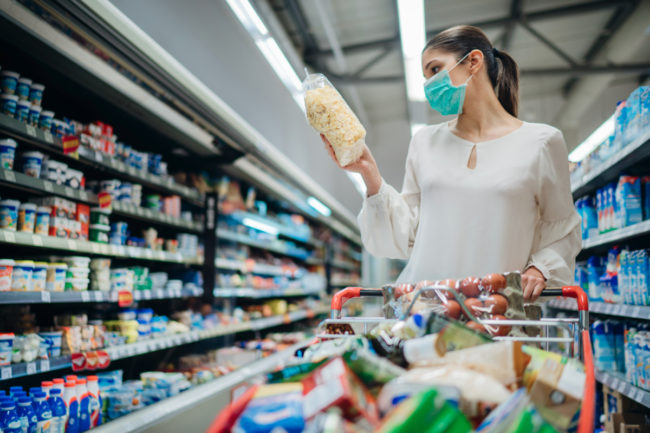 Woman wearing face mask grocery shopping for packaged foods