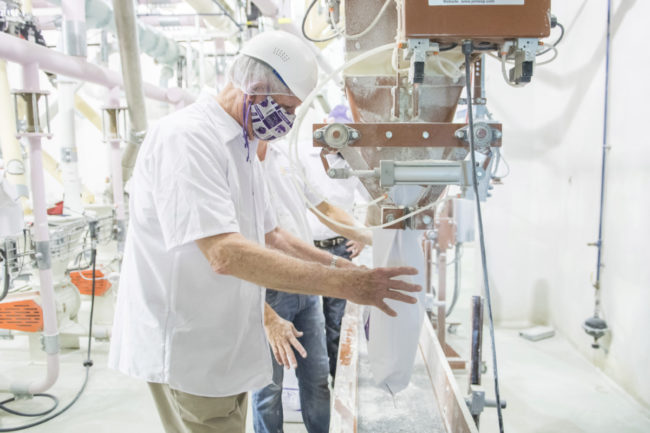 Richard Myers, president of Kansas State University, assists with the flour production on June 4 at the Hal Ross Flour Mill. Photos courtesy of KSU.