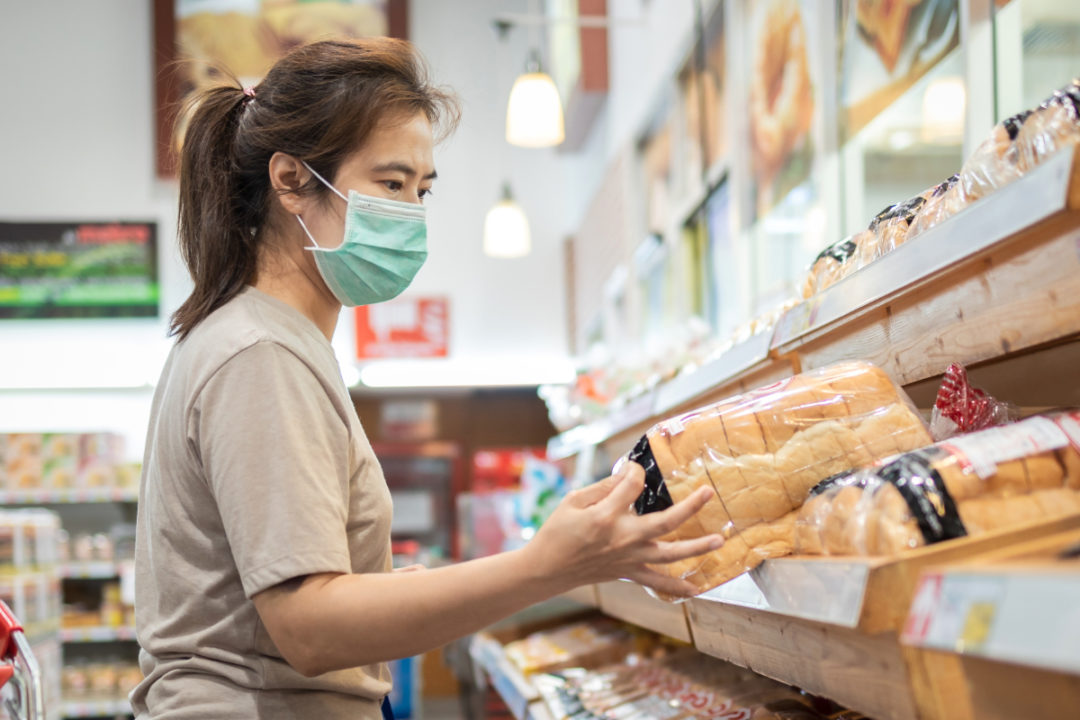Masked woman shopping in supermarket for bread during coronavirus pandemic