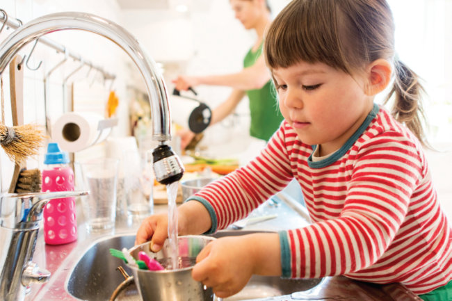 Child helping parents in the kitchen