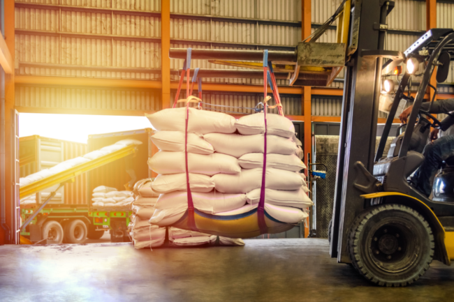 Forklift handling sugar bag for stuffing into container for export.
