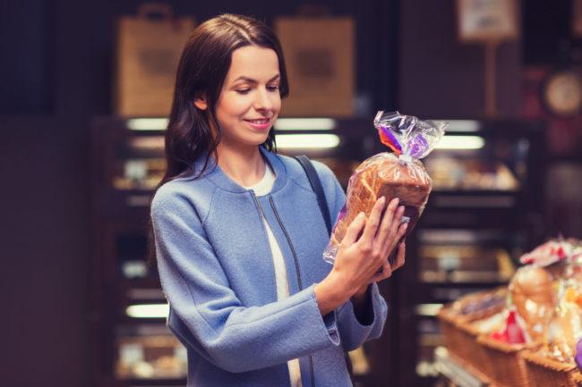 Consumer reading bread label in supermarket