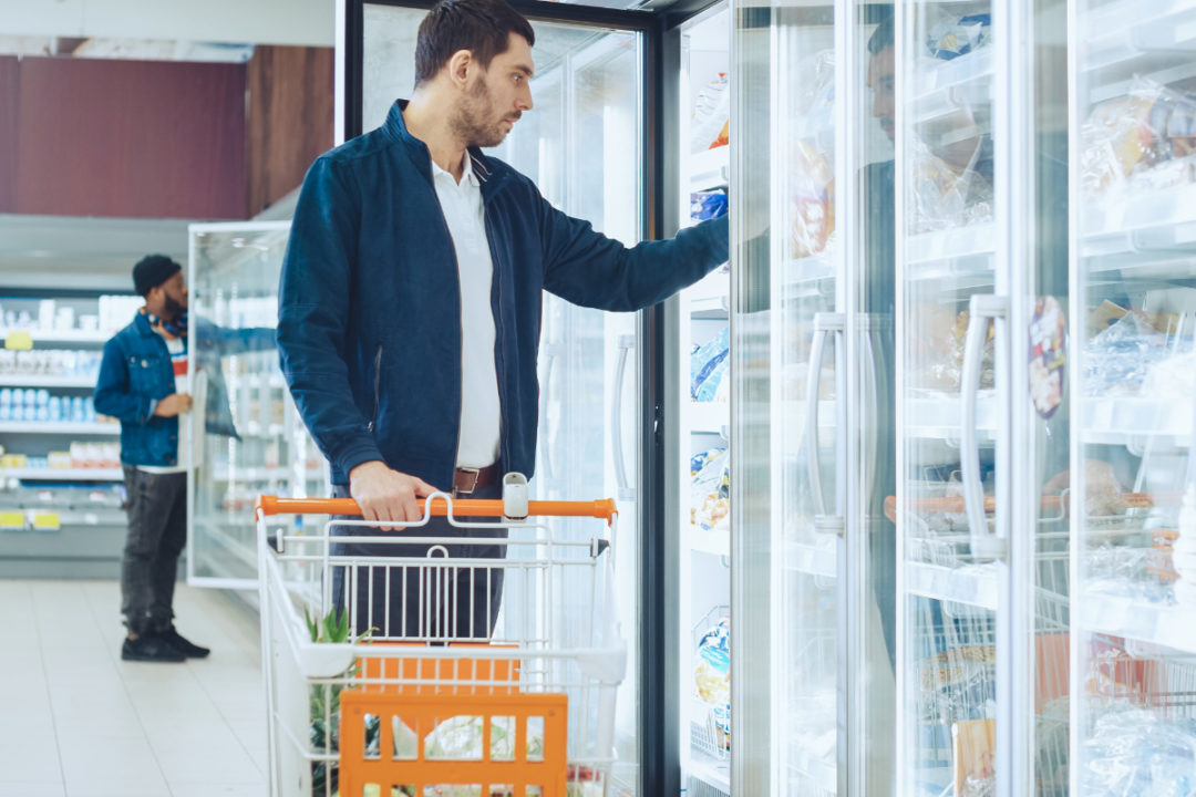 Men shopping in the frozen aisle at the supermarket