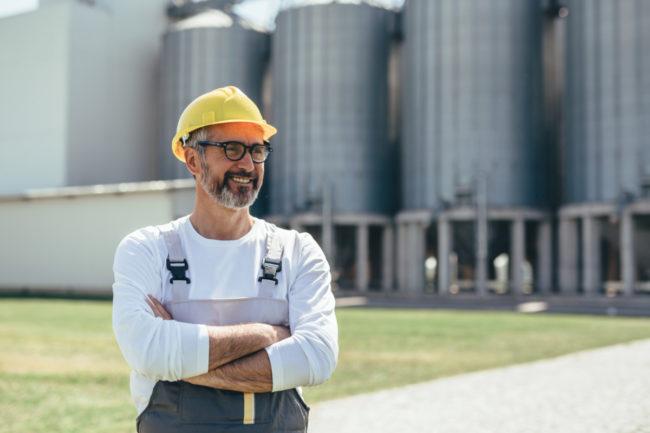 Worker in front of grain silos