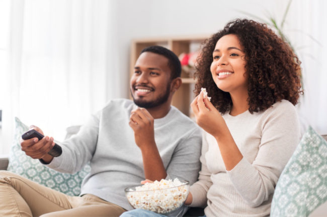 Couple eating popcorn while watching TV
