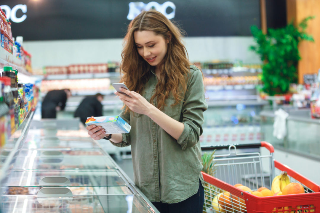 Woman grocery shopping while using smartphone to look up products