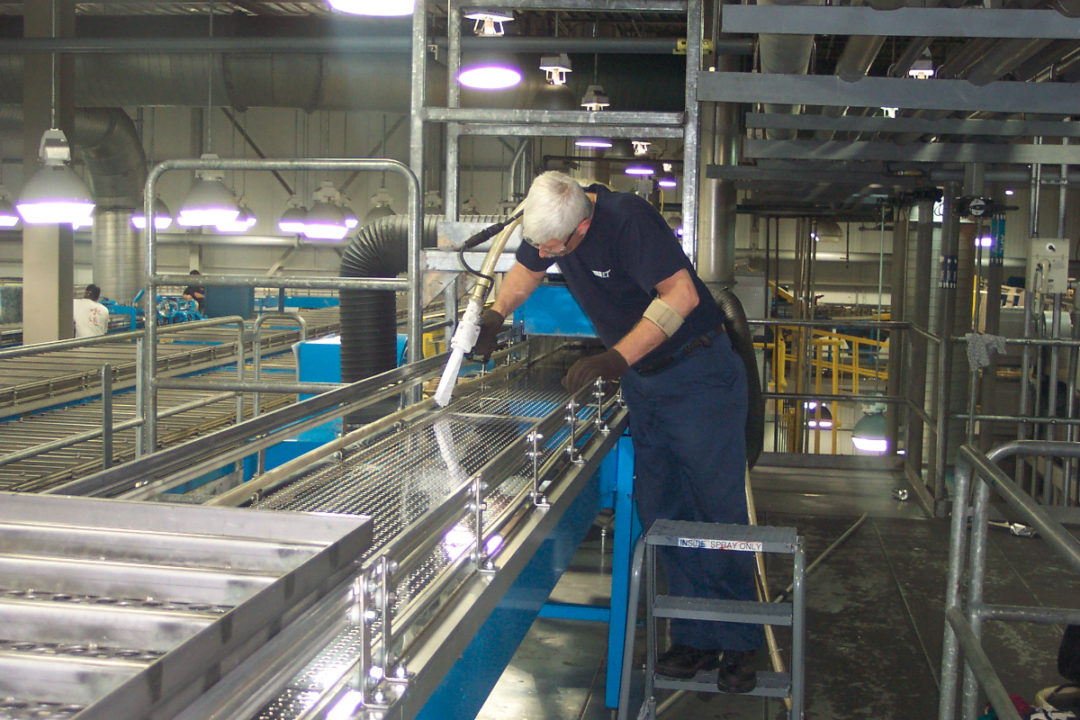 Man cleaning bakery equipment