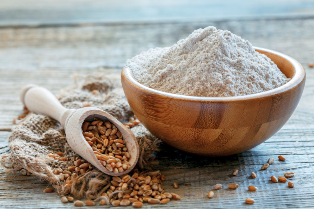 Whole wheat flour in a bowl and scoop