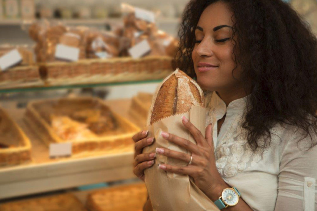 Woman smelling loaf of bread