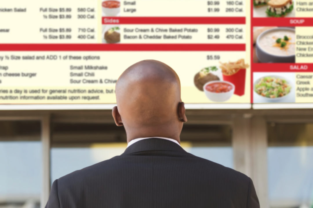Man ordering from menu board with posted calories