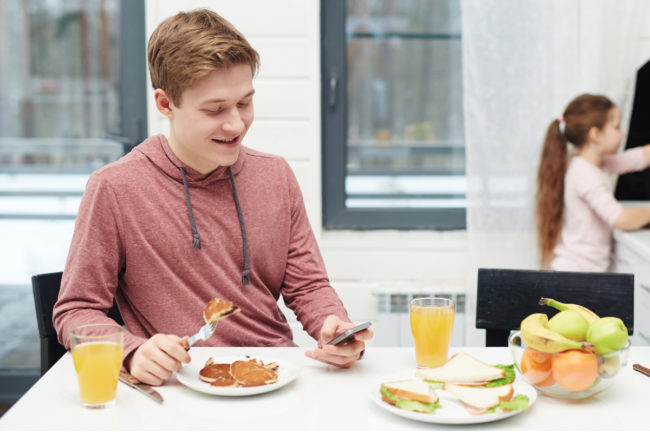 Gen Z boy eating and looking at phone