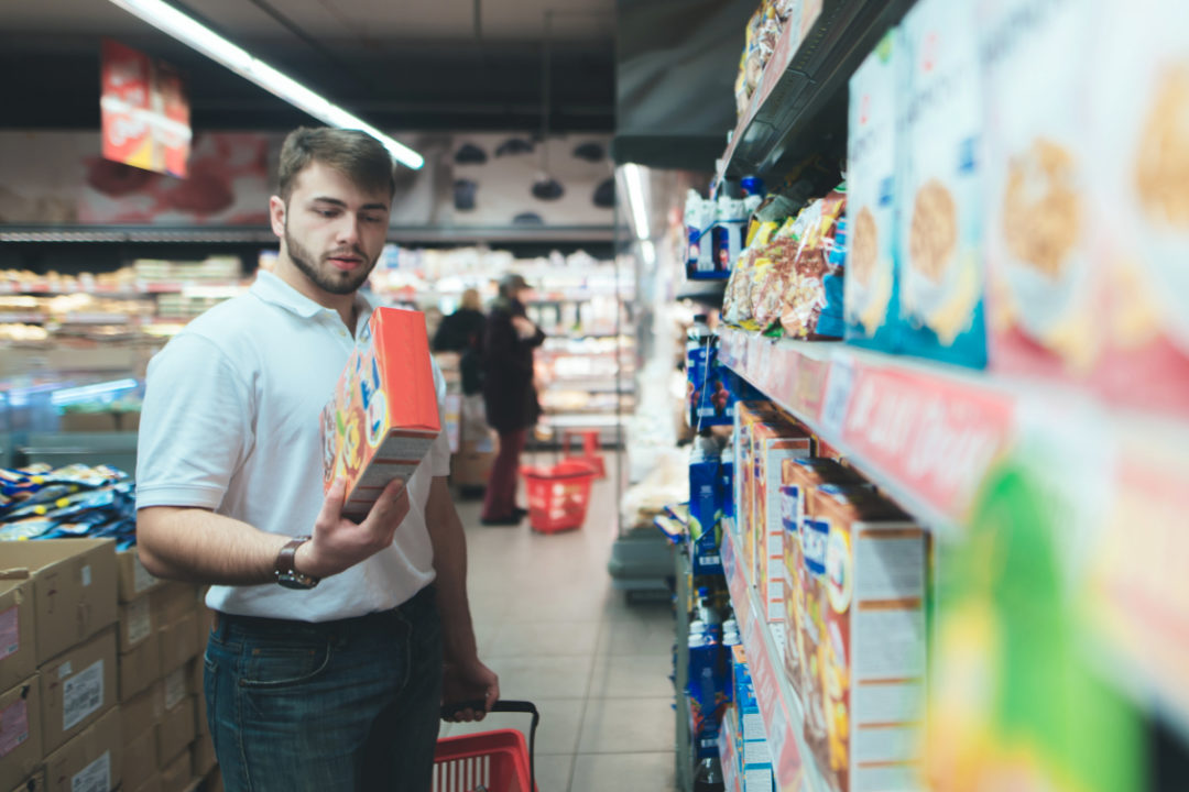 Man reading packaged food in grocery store