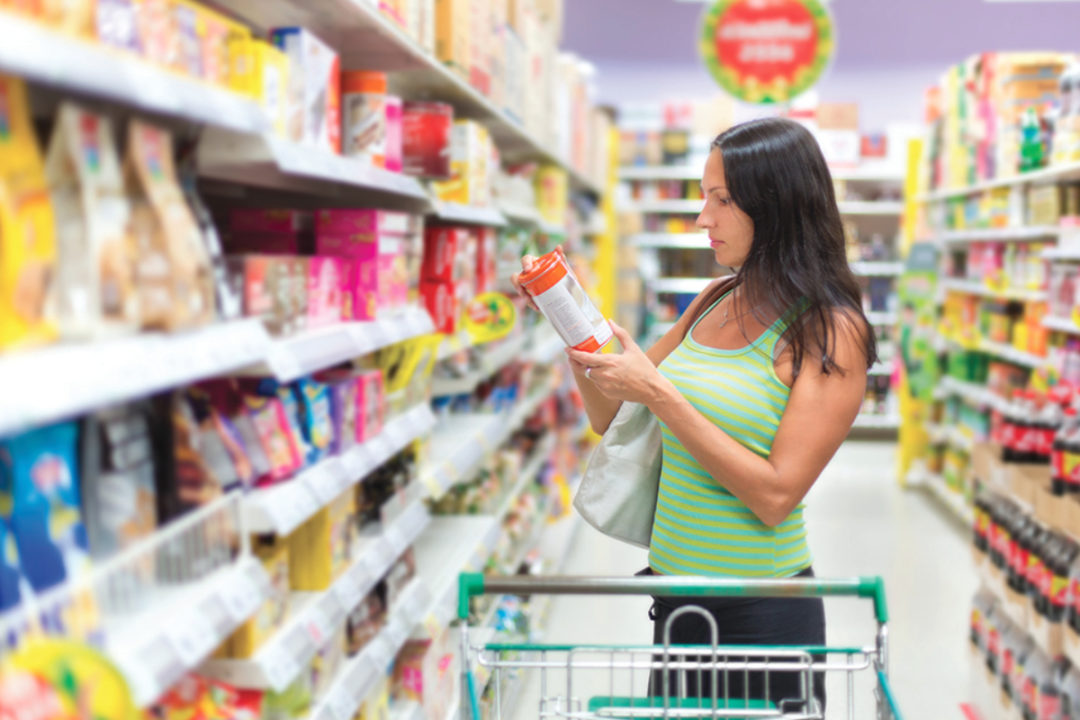 Woman reading product label at grocery store