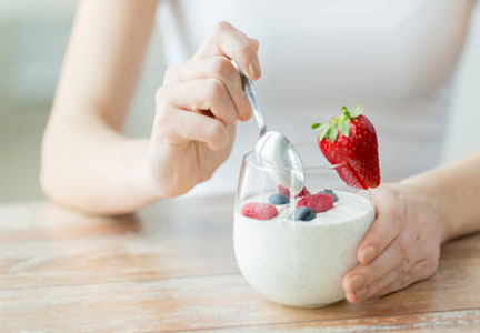 Young woman eating yogurt and berries for breakfast