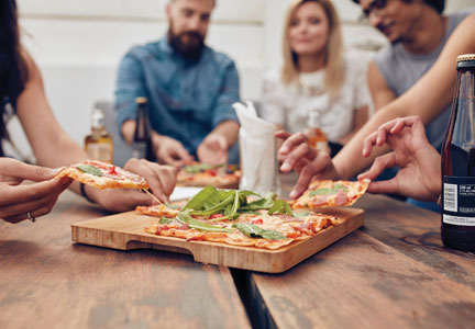 Millennials eating pizza at bakery