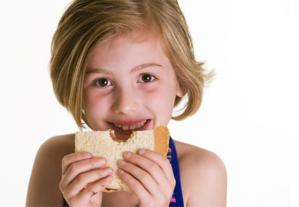 Child eating peanut butter and jelly sandwich