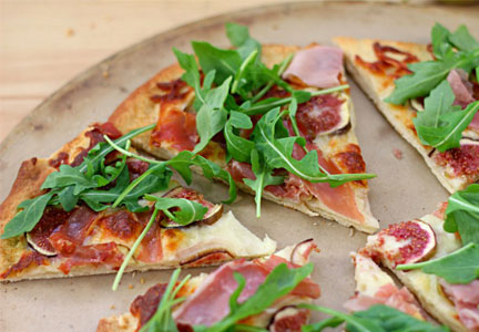 Pizza topped with prosciutto, fig and arugula