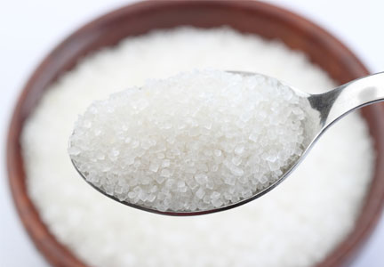 Sugar spooned from a bowl